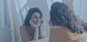 A happy woman smiling at herself in the mirror