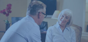 An elderly counselor smiling at her elderly male client